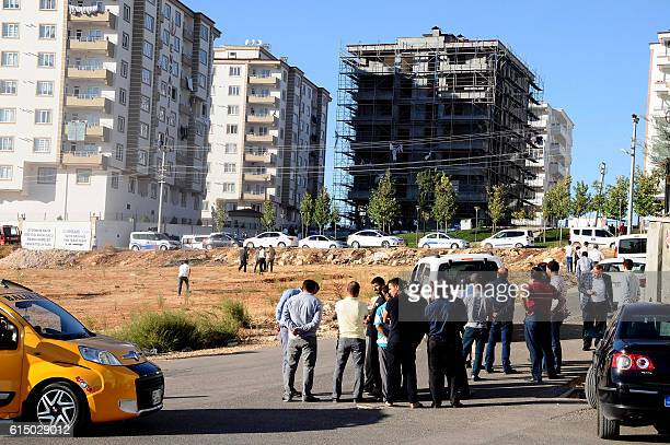 People gather as they look at the explosion site on October 16 2016 near the Syrian border in Gaziantep after a bomber blew himself up A suspected...