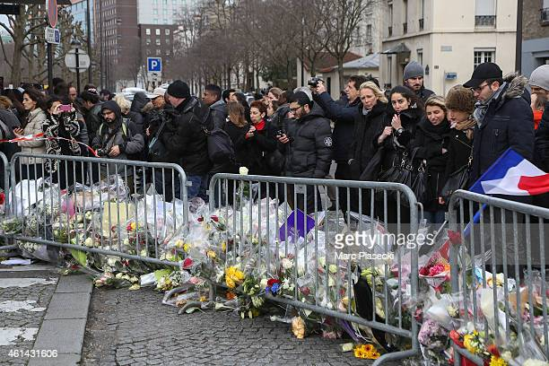 People gather as tributes are left in the area while Benjamin Netanyahu Prime Minister of Israel pays his respects at the Hyper Cacher following the...
