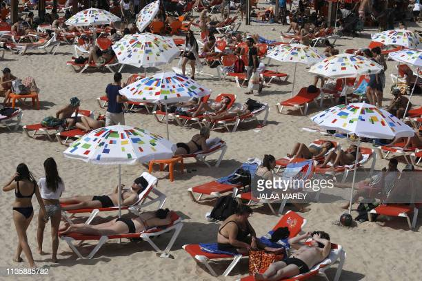 People gather at a beach in the Israeli coastal city of Tel Aviv on April 9 2019