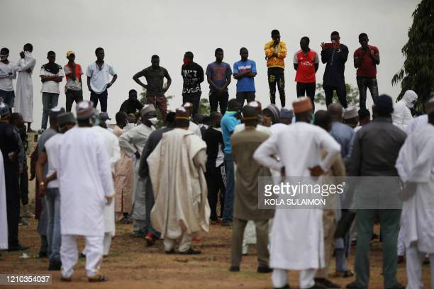 People gather at a burial ground in Gudu Abuja on April 18 where Nigerias Chief of Staff Abba Kyari will be buried Abba Kyari the chief of staff and...