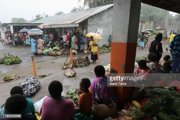 People gather at a local produce market during the first significant local rainfall in months in an extended dry season on December 06 2019 in Tanna...