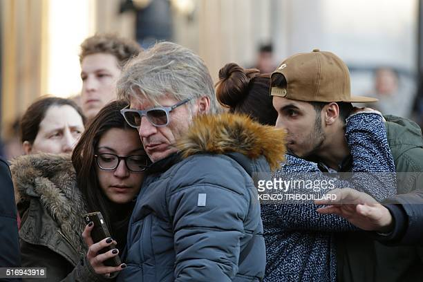 People gather at a makeshift memorial at Place de la Bourse following attacks in Brussels on March 22 2016 Airlines cancelled hundreds of flights and...