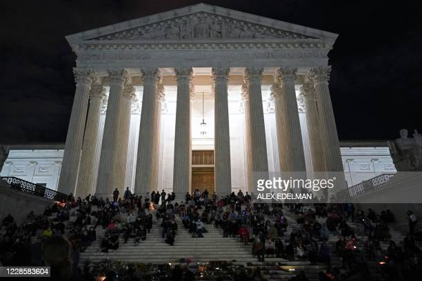 People gather at a makeshift memorial for late Justice Ruth Bader Ginsburg on the steps of the Supreme Court buidling, in Washington, DC, on...