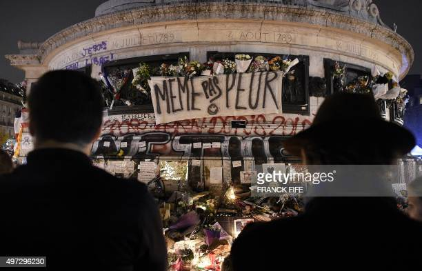 People gather at a makeshift memorial for the victims of Paris' attacks at the Place de la Republique in Paris on November 15 two days after a series...