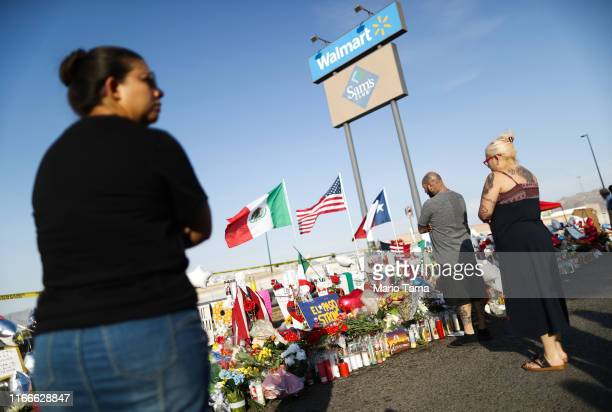 People gather at a makeshift memorial honoring victims outside Walmart near the scene of a mass shooting which left at least 22 people dead on August...