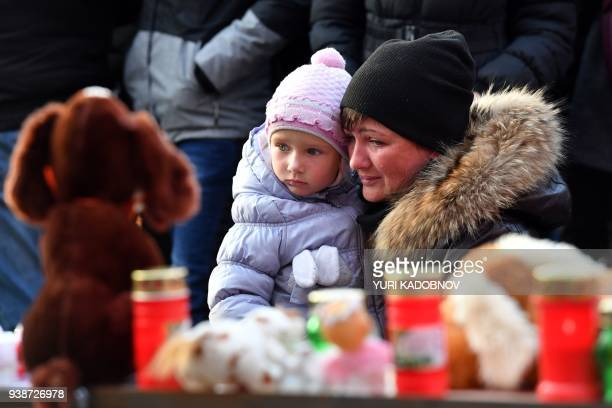 TOPSHOT People gather at a makeshift memorial on Manezhnaya Square to pay tribute to the victims of a Siberian shopping mall fire in downtown Moscow...