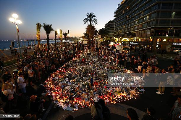 TOPSHOT People gather at a makeshift memorial on the Promenade des Anglais in Nice on July 17 in tribute to the victims of the Bastille Day attack...