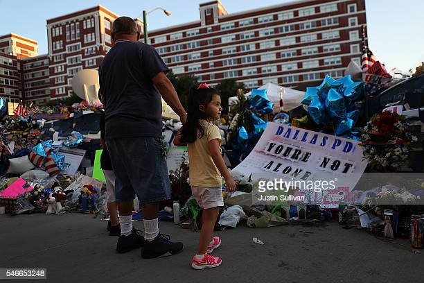 People gather at a makeshift memorial outside of the Dallas police department headquarters on July 12 2016 in Dallas Texas Funerals are set to begin...