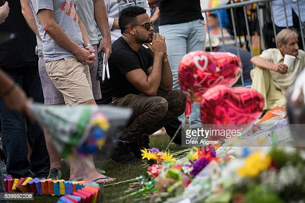 People gather at a makeshift memorial prior to an evening vigil for the victims of the Pulse Nightclub shootings at the Dr Phillips Center for the...
