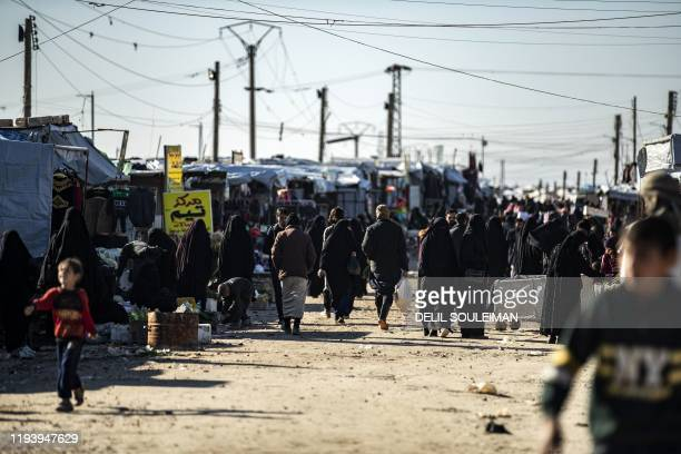 People gather at a market inside the Kurdishrun alHol camp for the displaced in the alHasakeh governorate in northeastern Syria on January 14 at the...