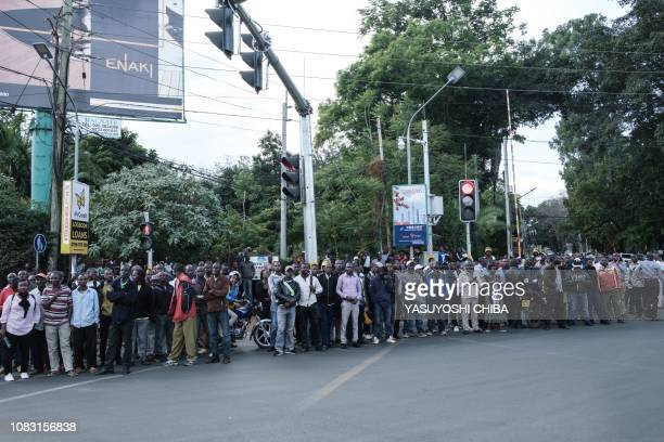 People gather at a road block point settled by the police after a blast followed by a gun battle rocked a upmarket hotel complex in Nairobi on...