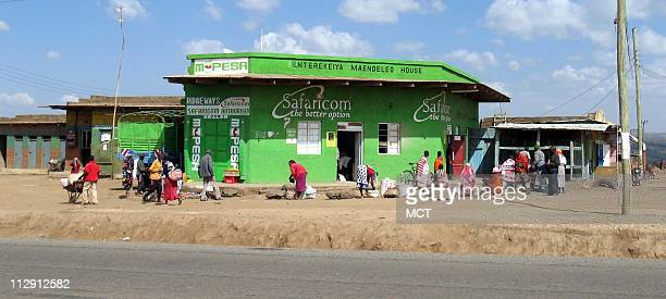 People gather at a Safaricom MPesa outlet in Ntulele Kenya The mobile phone company's pioneering money transfer system has signed up 55 million...
