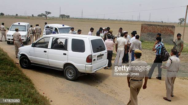 People gather at a scene where Gurgaon police claim to killed one gangster Virendar aka Kana in an encounter at Dhankot on July 4 2012 in Gurgaon...