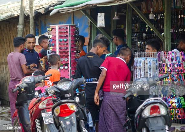 People gather at a shop at the Aung Mingalar quarter for Rohingya Muslims as they observe the first day of the Eid al-Fitr holiday, which marks the...