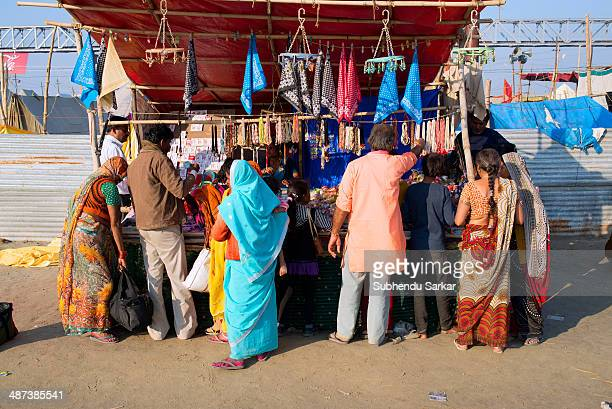 People gather at a shop on the fair ground of maha Kumbh mela. Kumbh Mela is a site of mass pilgrimage in which Hindus gather at a sacred river for a...