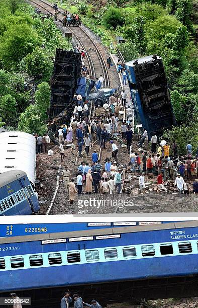 People gather at a site where a train derailled over a bridge near Amboli village between Veer and Karanjadi stations 16 June 2004 about 200...
