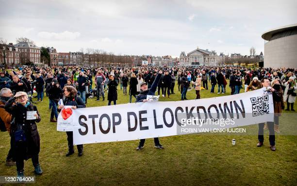 People gather at Amsterdam's Museumplein during a portest against the lockdown imposed to curb the spread of the Covid-19 pandemic and the outgoing...