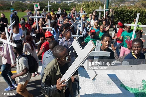 People gather at Cape Town University on August 20 2015 to mark the third anniversary of the Marikana massacre of 34 striking platinum miners near...