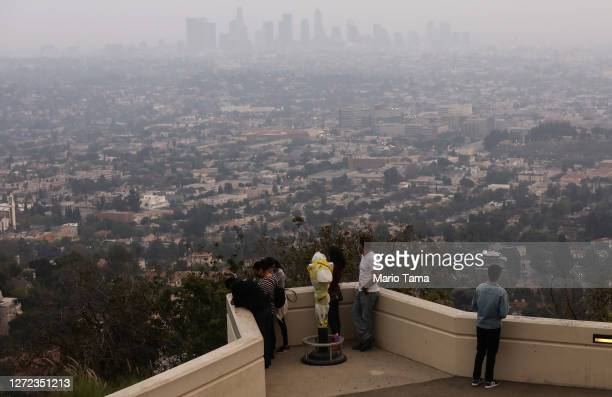 People gather at Griffith Observatory before sunset as the downtown skyline is partially obscured by smoke from wildfires on September 13, 2020 in...