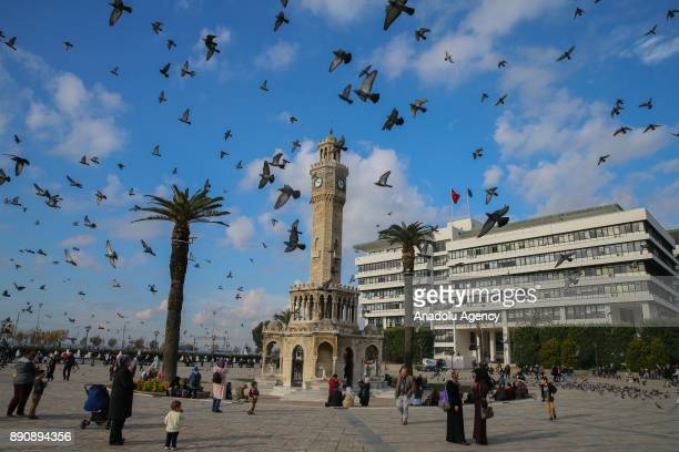 People gather at Konak Square as birds fly over them on a warm day despite cold weather surrounds most of the country in Izmir Turkey on December 12...
