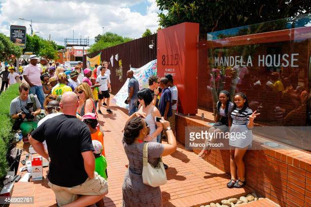 People gather at Nelson Mandela's old house as the former South African President is laid to rest in Qunu on December 15 2013 in Soweto Johannesburg...