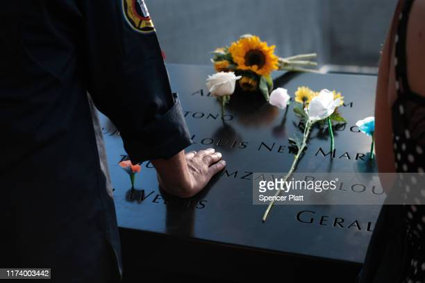 People gather at one of the pools at the National September 11 Memorial following a morning commemoration ceremony for the victims of the terrorist...