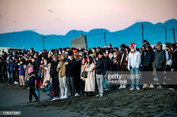 People gather at Southern Beach of Chigasaki to watch the sunrise on New Year's Day in Kanagawa Prefecture, southwest of Tokyo on January 1, 2021.