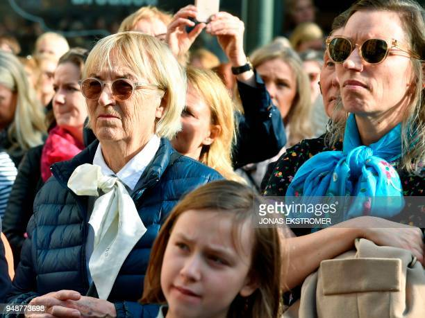 People gather at Stortorget square in Stockholm while the Swedish Academy held its weekly meeting at the Old Stock Exchange building seen in the...