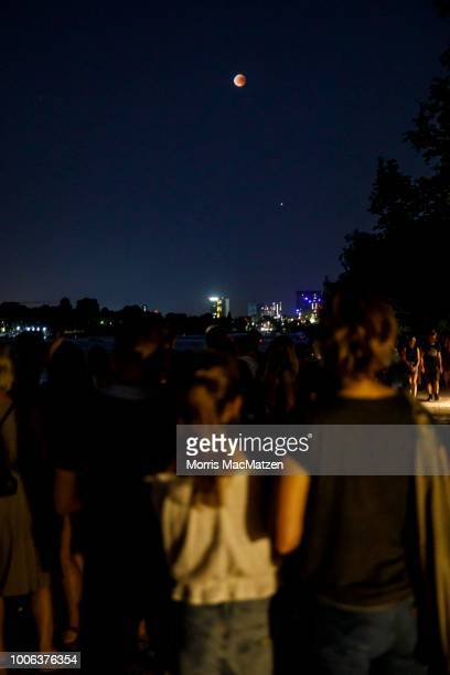 People gather at the Alster Lake to watch the 'blood moon' eclipse over the northern German city of Hamburg on July 27 2018 During this eclipse when...