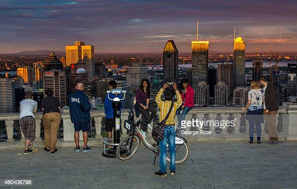 People gather at the Belvedere Overlook in Mont Royal Park to view the city and take pictures at sunset on June 30 2015 in Montreal Quebec Canada...