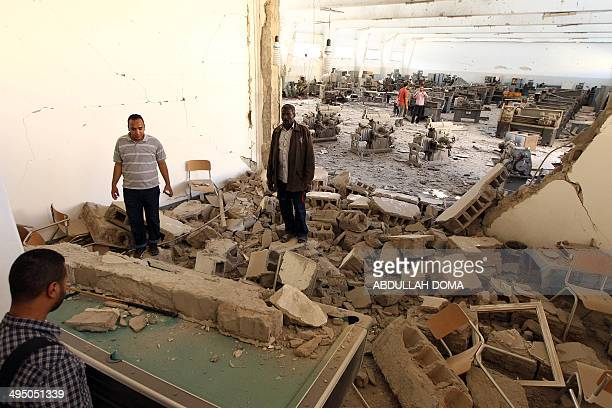 People gather at the Faculty of Mechanical Engineering Technology following an airraid that missed its target in the eastern Libyan city of Benghazi...
