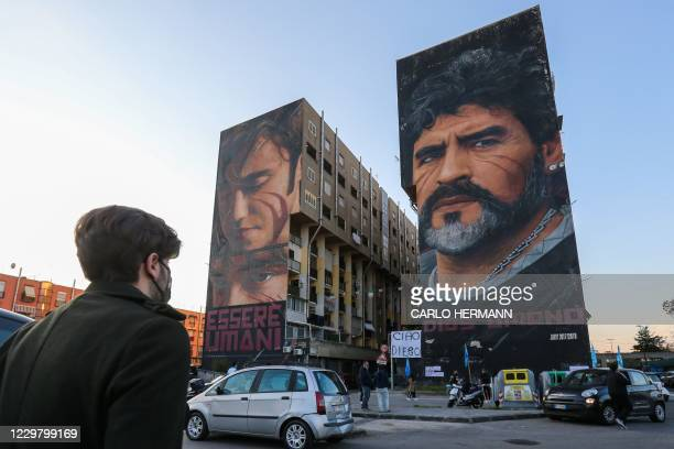 People gather at the foot of a mural of late Argentinian football legend Diego Maradona on November 26, 2020 in Naples, southern Italy, to mourn his...