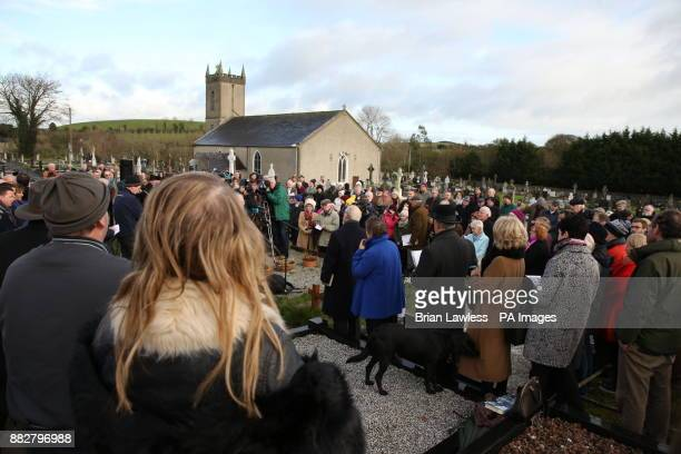 People gather at the graveside of Irish poet Patrick Kavanagh in Inniskeen as they mark the 50th anniversary of his death