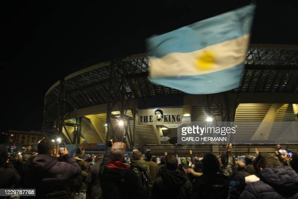 People gather at the main entrance of the San Paolo stadium in Naples on November 25, 2020 in front of an image of Argentinian football legend Diego...
