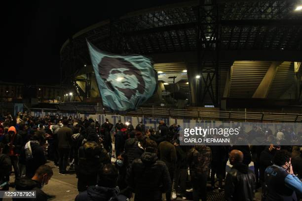 People gather at the main entrance of the San Paolo stadium in Naples on November 25, 2020 waving a flag at the effigy of Argentinian football legend...