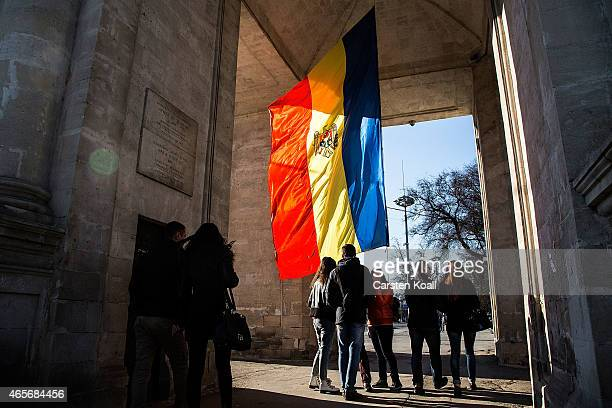 People gather at the Moldovan national flag at the parliament building on March 8 2015 in Chisinau Moldova The Republic of Moldova is a landlocked...