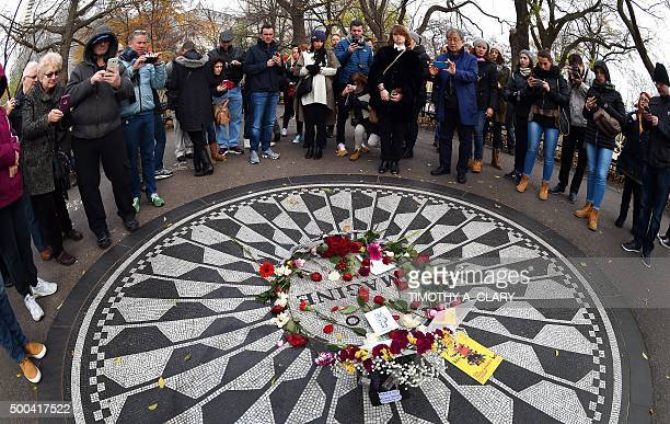 People gather at the mosaic named for the John Lennon's song Imagine December 8 2015 at Strawberry Fields the Central Park garden dedicated in his...