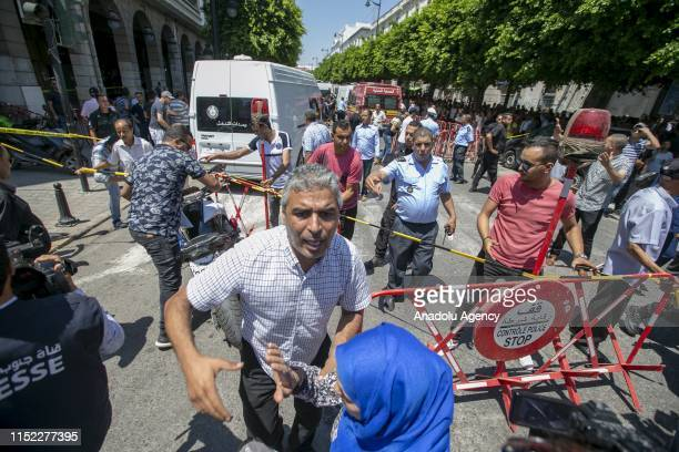 People gather at the scene after a suicide bombing targeted a police vehicle in the Tunisian capital in Tunis, Tunisia on June 27, 2019. At least one...