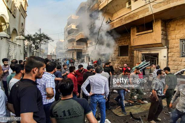 People gather at the scene of a car bomb explosion outside the Syriac Orthodox Church of the Virgin Mary in the predominantly Christian neighbourhood...