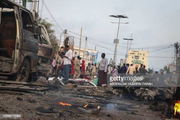 TOPSHOT People gather at the scene of twin car bombs that exploded within moments of each other in the Somali capital Mogadishu on November 9 2018 At...