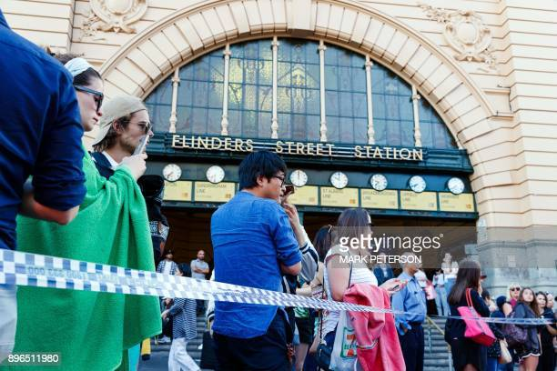 People gather at the scene of where a car ran over pedestrians in Flinders Street in Melbourne on December 21 2017 The car ploughed into a crowd in...