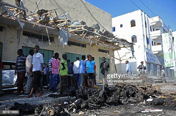 People gather at the site of a bomb blast near Makka alMukarama Road in the Somali capital Mogadishu on December 19 2015 Several people were killed...