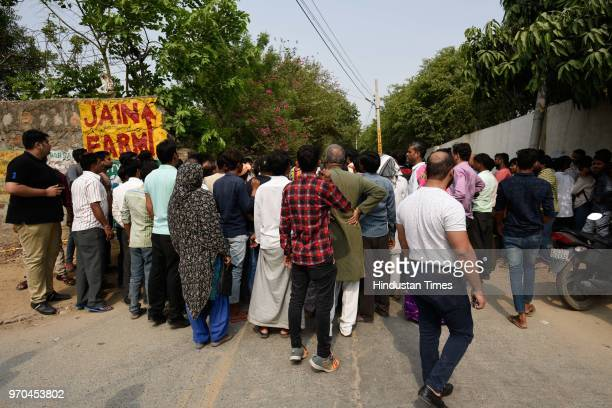 People gather at the site of an encounter between the Special Cell and a gang of criminals in the Fatehpur Beris Chanan Hola village near Chhatarpur...