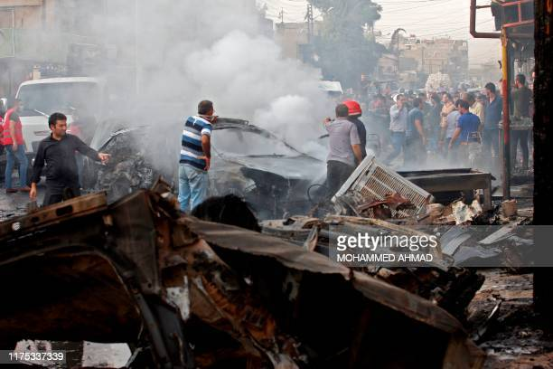 People gather at the site of an explosion in the northeastern Syrian Kurdish city of Qamishli on October 11, 2019. - An explosives-laden vehicle...