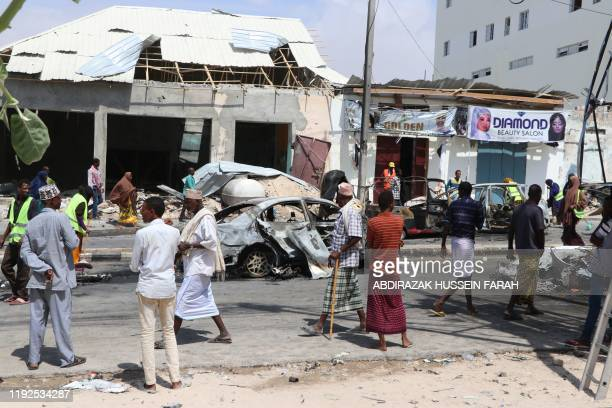 TOPSHOT People gather at the site where a car bomb exploded near the Somali parliament in Mogadishu Somalia on January 8 2020 At least four people...