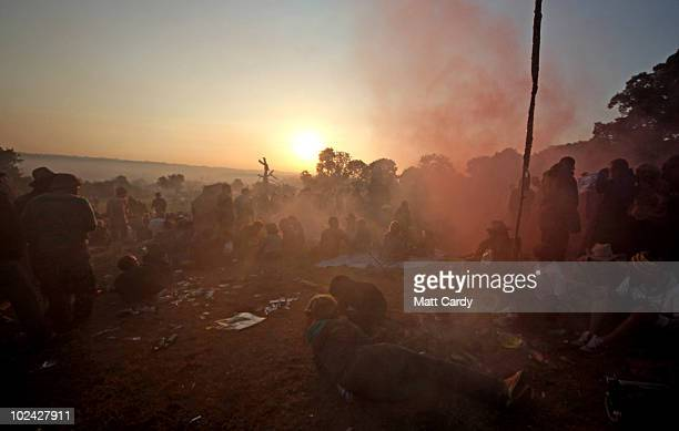 People gather at the stone circle as the sun rises over the 2010 40th Glastonbury Festival at Worthy Farm Pilton on June 26 2010 in Glastonbury...