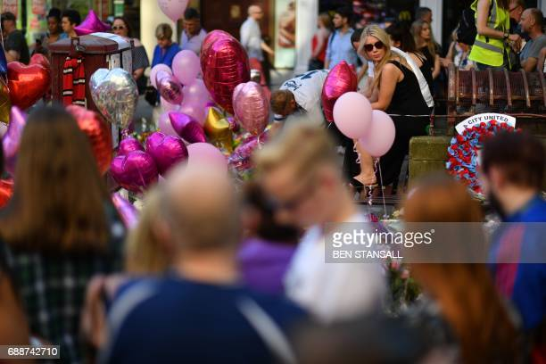 People gather at the tributes in St Ann's Square in central Manchester northwest England on May 26 following the May 22 terror attack at the...