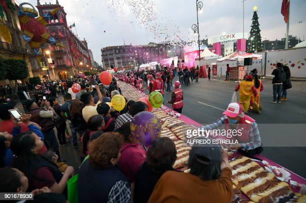 People gather at the Zocalo square in Mexico City to get a piece of traditional 'Rosca de Reyes' on Epiphany's eve on January 5 2018 The giant cake...