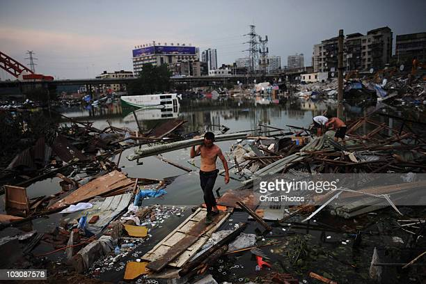 People gather belongings as parking lot and freight yard submerged by floods are being demolished near water area where the Yangtze River and...