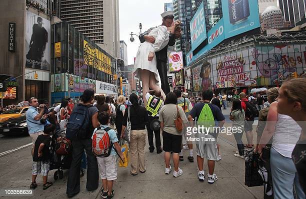 People gather beneath a 26foot statue inspired by the iconic kiss between a nurse and a sailor in Times Square August 12 2010 in New York City Alfred...